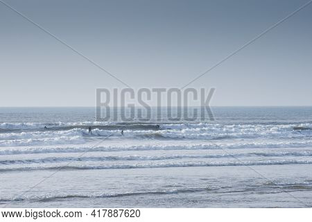 Group Of People Are Surfing And Catching Waves In The Ocean