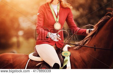 A Woman With A Medal Around Her Neck Sits In The Saddle On A Sorrel Racehorse, Which Is Awarded A Ro