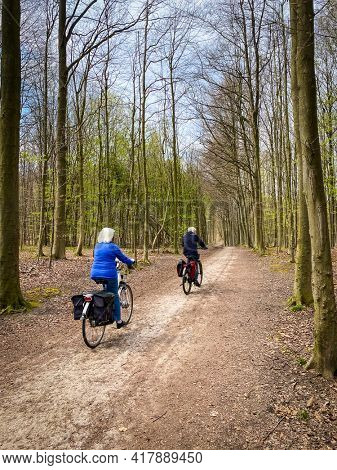 Two elderly caucasian people riding a bicycle in Sonian Forest, close to Brussels aera, Belgium