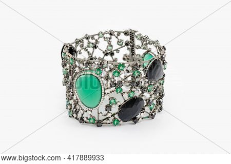 Fashion Bracelet With Diamonds And Emerald Natural Gem Stones On Gray Background. Green And Black Pr