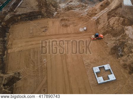 Drone View Of Construction Site. Vibration Road Roller Leveling The Ground For Construct Of Foundati
