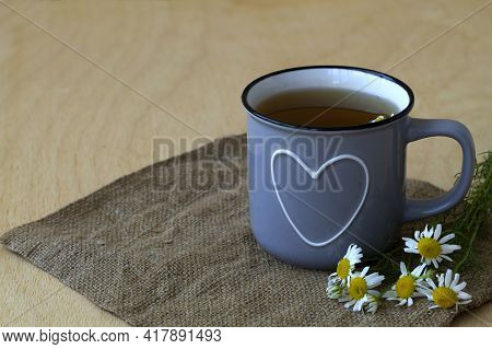 Grey Mug Of Chamomile Tea On Sackcloth. Blue Cup Of Hot Herbal Chamomile Tea On A Wooden Table With
