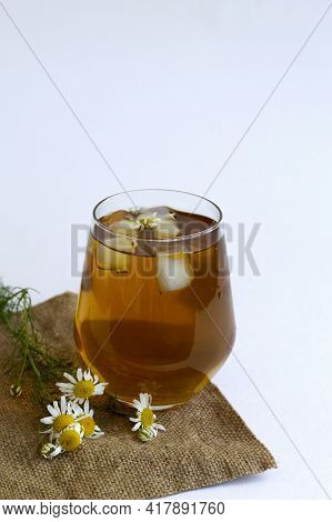 Chamomile Tea On Sackcloth. Glass Cup Of Iced Herbal Chamomile Tea On A White Table With Copy Space.