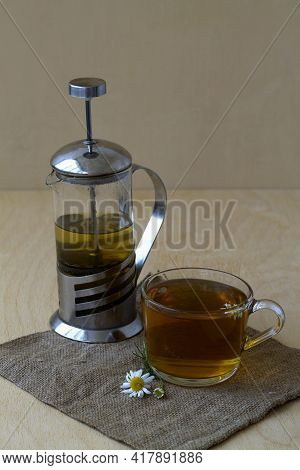 Glass Cup Of Hot Herbal Chamomile Tea With Teapot On A Wooden Table With Copy Space With Fresh Flowe