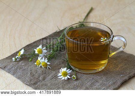 Cup Of Herbal Tea.mug Of Chamomile Tea On Sackcloth. Glass Cup Of Hot Herbal Chamomile Tea On A Wood