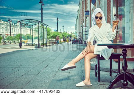 Glamorous young woman in a white terry dressing gown with a white towel on her head with sunglasses sits at a table in a street cafe holding glass of wine in her hand.