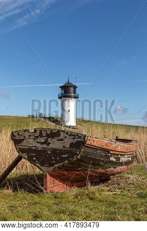 Small lighthouse at Cuxhaven, known as Dicke Bertha, old wooden boat in foreground
