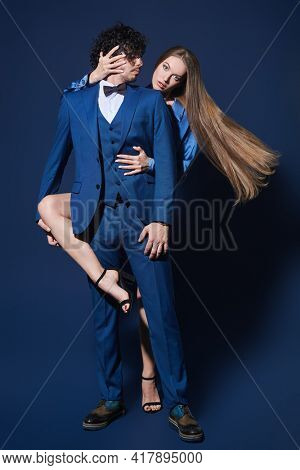Handsome man in elegant classic suit dancing tango with a beautiful blonde girl in evening dress. Full length portrait on a dark blue backround.