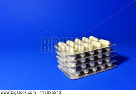 Pills In Capsules In Packpage On Blue Background. Medicine Grade Pharmaceutical Tablets. Medical Pil