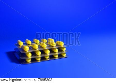 Yellow Pills In Capsules In Packpage On Blue Background. Medicine Grade Pharmaceutical Tablets. Medi