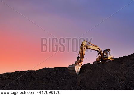 Excavator Working On Earthmoving At Open Pit Mining On Sunset Background. Backhoe Digs Sand And Grav