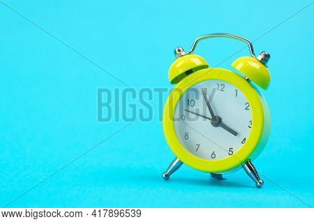 Yellow Retro Alarm Clock Close-up With Place For Text. Alarm Clock In The Old Style On A Blue Backgr