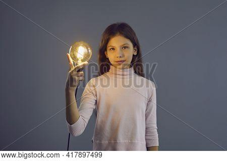Smart Intelligent Pre-teen Schoolgirl Holding Idea Lamp Studio Shot On Grey Wall