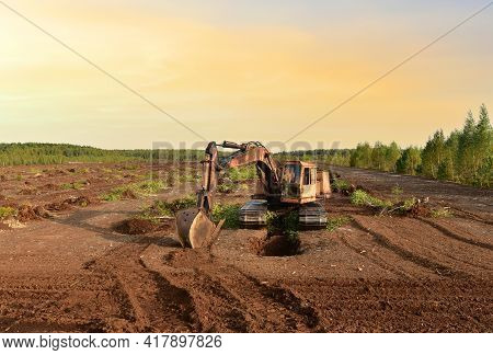 Excavator Digging Drainage Ditch In Peat Extraction Site. Drainage Of Peat Bogs And Destruction Of T
