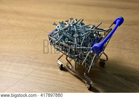 Self-tapping Screws In A Shopping Cart On Wooden A Table. Screw For Working With Wood Products And S