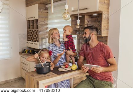 Cheerful Young Family Having Fun Cooking Lunch Together, Sitting At Kitchen Counter And Enjoying Lei