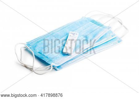 Covid-19 rapid antigen test. Rapid antibodies test kit and protective medical face mask isolated on white background.