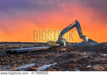 Excavator Excavating At A Construction Site Against The Backdrop Of Sunset. Natural Gas Pipeline Lay