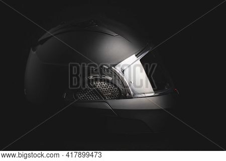 Black modular motorcycle helmet on black background.