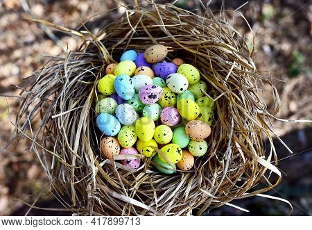 Multi-colored Easter Eggs In A Bird's Nest. Straw And Twig Bird Nest With Egg. Easter Is A Christian