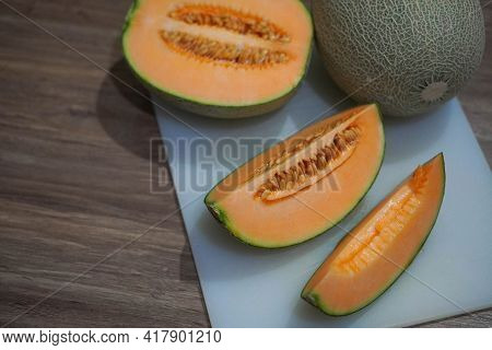 Cut Watermelon Cantaloupe And Watermelon Cantaloupe On White Chopping Board, Wooden Floor Background