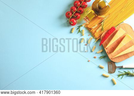 Uncooked Pasta On Blue Background. Top View. Raw Pasta With Ingredients For Cooking. Food Concept. I