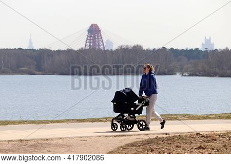 Moscow, Russia - April 2021: Woman With Baby Pram Walking On River Background In Spring City