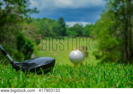 Golf Ball On Tee And Golf Club In A Beautiful Golf Course With Morning Sunshine.  Ready For Golf In