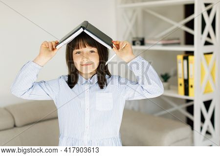 Portrait Of Nice Attractive Pre-teen Girl Doing Class Home Work Task In Living Room At The Sofa. Edu