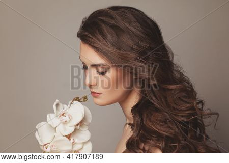 Young Beautiful Model Woman With Long Brown Curly Hairdo Portrait