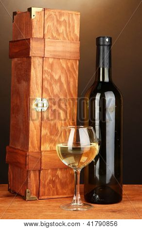 Wooden case with wine bottle on wooden table on brown background