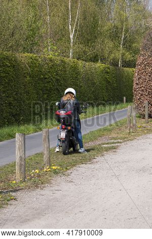 Sint Gillis Waas, Belgium, April 21, 2021, Girl On Scooter Stops And Looks At Her Smartphone