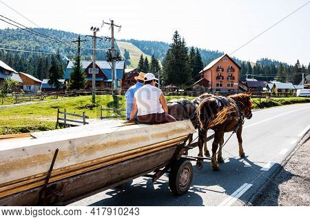 Horse Carriage With Wooden Planks On Mountain Road In Bihor, Romania, 2021
