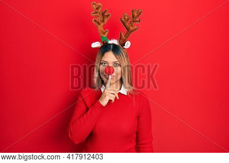 Beautiful hispanic woman wearing deer christmas hat and red nose asking to be quiet with finger on lips. silence and secret concept.