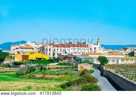 a view of Nulles, a small farming village in Tarragona Province in Catalonia, Spain, higlighting the bell tower of its church, dedicated to Saint John the Baptist