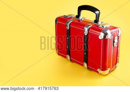 Red Suitcase On A Yellow Background. Travel Suitcase For Travel. Concept. Place For Your Text.