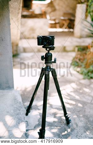 Black Digital Camera Sits On A Tripod On The Sidewalk. Front View