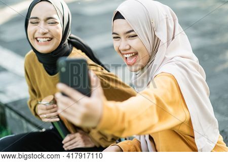 Two Girls Wearing Hijab Laughing When Looking Video Together With Smartphone In The Afternoon