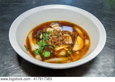 Chinese Roll Noodle Soup With Crispy Pork, Boiled Egg, Pork Blood Served On White Bowl. Thai Languag