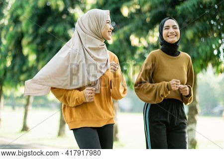 Two Teenage Girls In Veil Do Outdoor Sports While Jogging Together