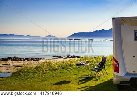 Camping On Sea Shore. Camper Car With Tourist Chairs And Table On Norwegian Fjord. Holidays Relaxati