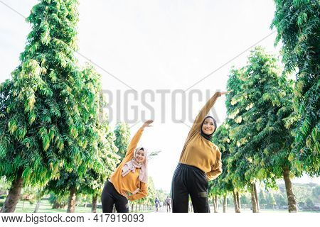 View From Below Of Two Girls In Veil Do Arm Stretches By Raising Their Arms Upward With Their Bodies