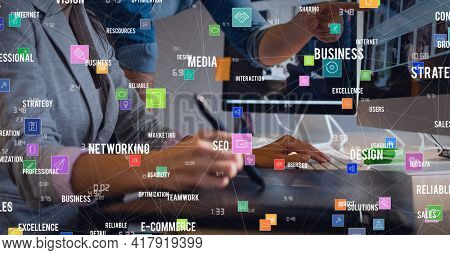 Composition of digital icons and business text over woman using computer and graphic tablet. global technology and digital interface concept digitally generated image.