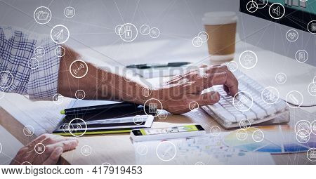 Composition of network of connections with digital icons over man typing on computer keyboard. global technology and digital interface concept digitally generated image.
