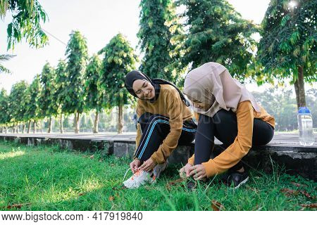 Two Girls In Headscarves Sit On The Floor Chatting While Holding Their Shoelaces In Preparation For