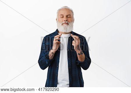 Hopeful Bearded Senior Man Cross Fingers, Making Wish, Hope Or Pray For Something, Close Eyes And Be