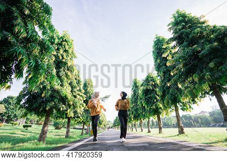 View From Below Of Two Girls In Veil Do Outdoor Sports While Jogging Together