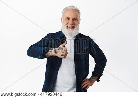 Cheerful Stylish Senior Man With Tattoos, Showing Thumbs Up And Laughing Pleased, Say Yes, Standing