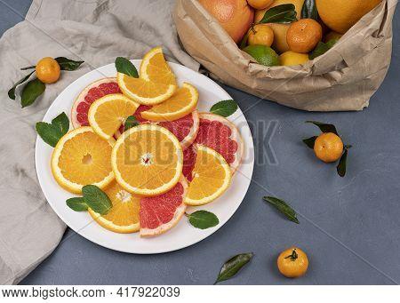 Fresh Sliced Citrus Fruits On A Plate. Orange, Grapefruit, Lemon, Lime, Tangerine On A Gray Table. A