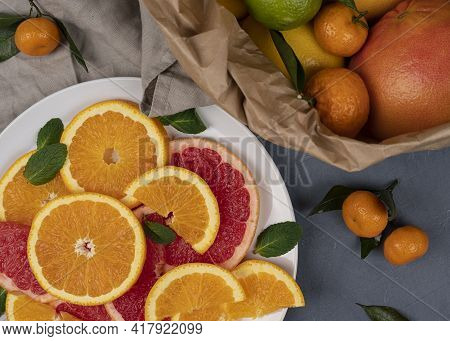 Various Citrus Fruits Border With Green Leaves On White Background. Top View. Halves Of Citrus. Vita